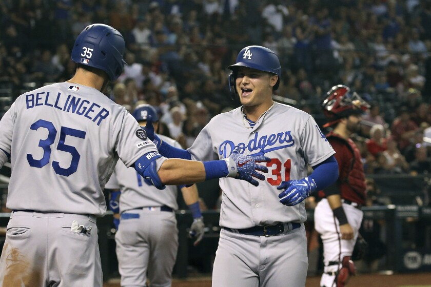 Joc Pederson is congratulated by Dodgers teammate Cody Bellinger after hitting a tiebreaking home run against the Diamondbacks in the 11th inning Sunday.
