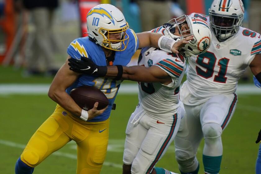 Miami Dolphins defensive back Nik Needham sacks Chargers quarterback Justin Herbert.