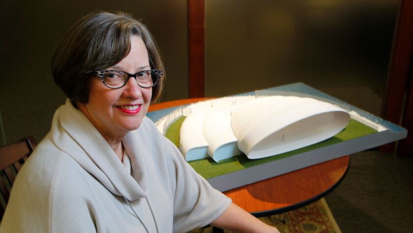 San Diego Symphony CEO Martha Gilmer sits next to an architect's model of the proposed Bayside Performance Park stage in downtown San Diego.