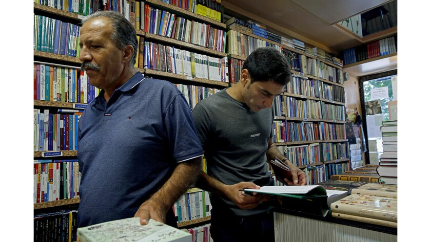 """Bookstore owner Mohammad Ali Behjat, left, and Kurdish customer Mohammad Rashidi. """"I'm looking for my identity,"""" said Rashidi, who holds an archaeology degree but works as a computer technician."""