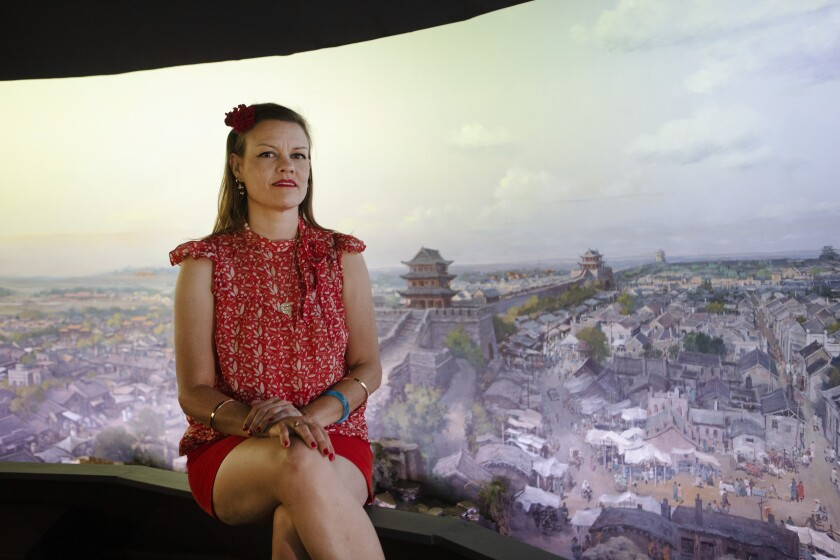 A woman in red sits for a portrait inside the Velaslavasay Panorama.
