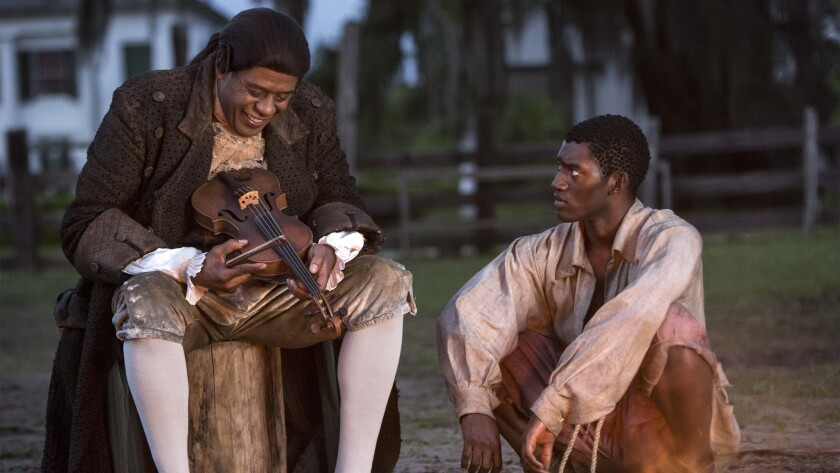 "Fiddler (Forest Whitaker), left, and Kunta Kinte (Malachi Kirby) talk in the re-imagining of ""Roots."""