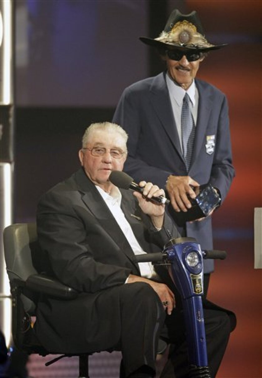 Maurice Petty, left, speaks as brother Richard Petty, right, looks on as they accept the induction of their father, lee Petty, into the NASCAR Hall of Fame during a ceremony in Charlotte, N.C., Monday, May 23, 2011. (AP Photo/Chuck Burton)