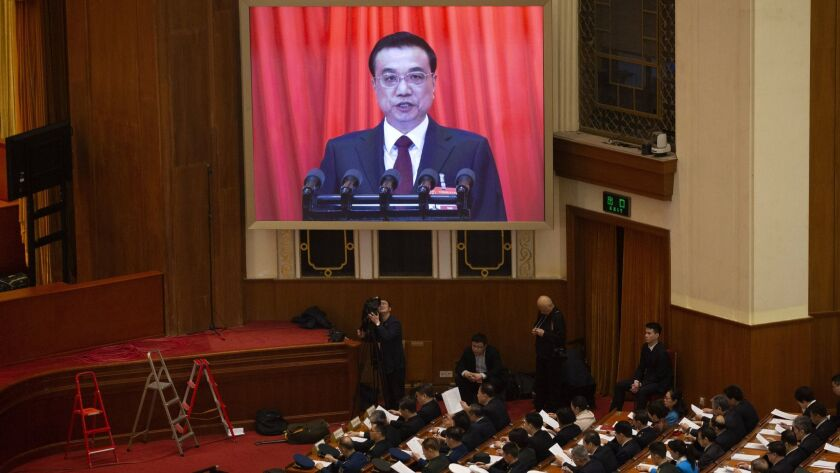 Chinese Premier Li Keqiang is seen on a big screen as he delivers the work report at the opening ses