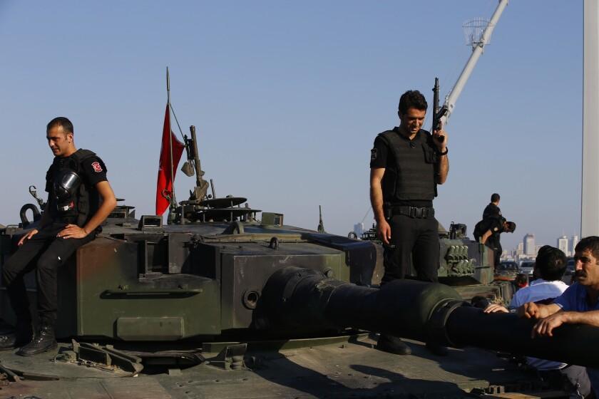 Agentes de policía turcos, leales al gobierno, alzados sobre tanques abandonados por militares turcos cerca del emblemático puente del Bósforo, en Estambul, el sábado 16 de julio de 2016. El presidente de Turquía, Recep Tayyip Erdogan, declaró el sábado de madrugada que tenía el control del país tras un intento de golpe de Estado. (AP Foto/Emrah Gurel)