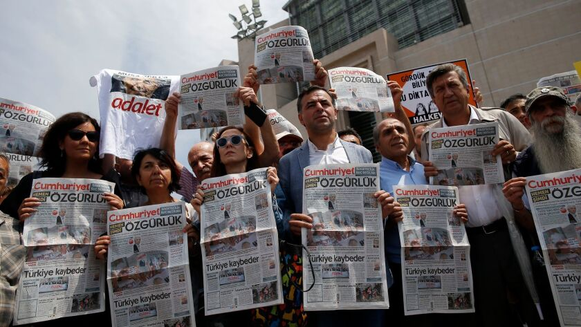 Journalists and activists gather outside the court in Istanbul, Friday, July 28, 2017, protesting ag