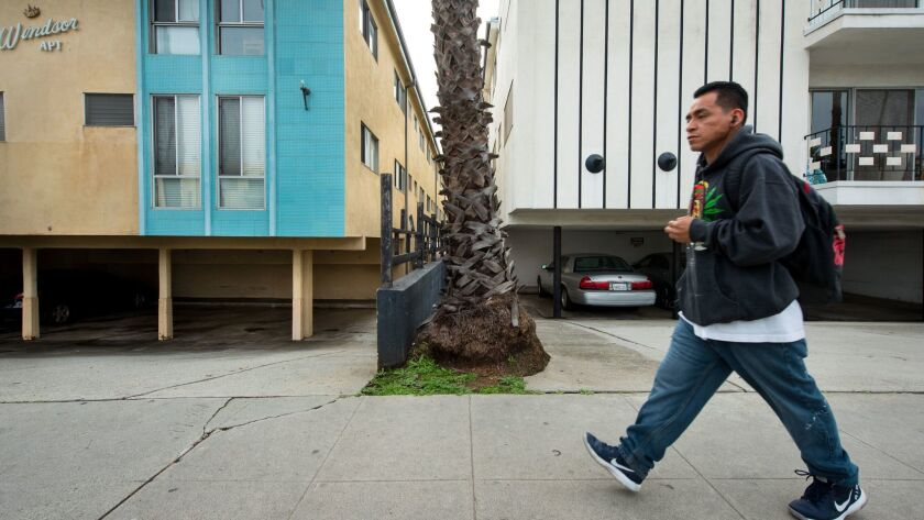 A person walks past apartment buildings in Santa Monica on Feb. 8.