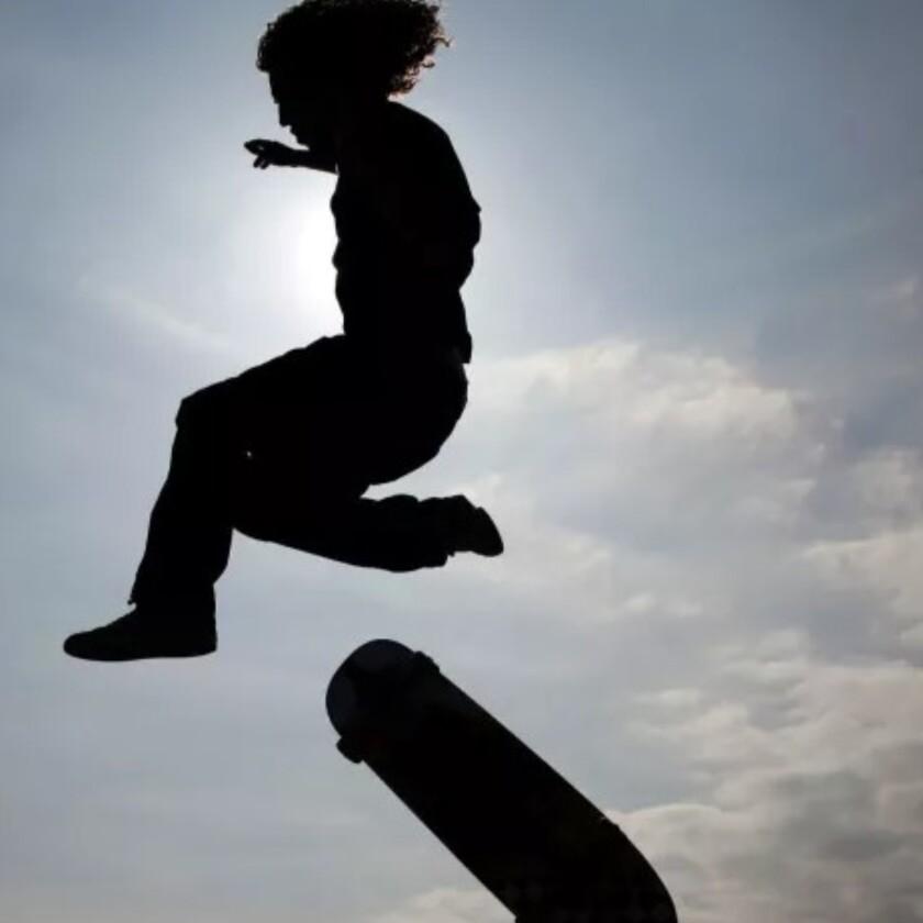 A boy jumps off his skateboard.
