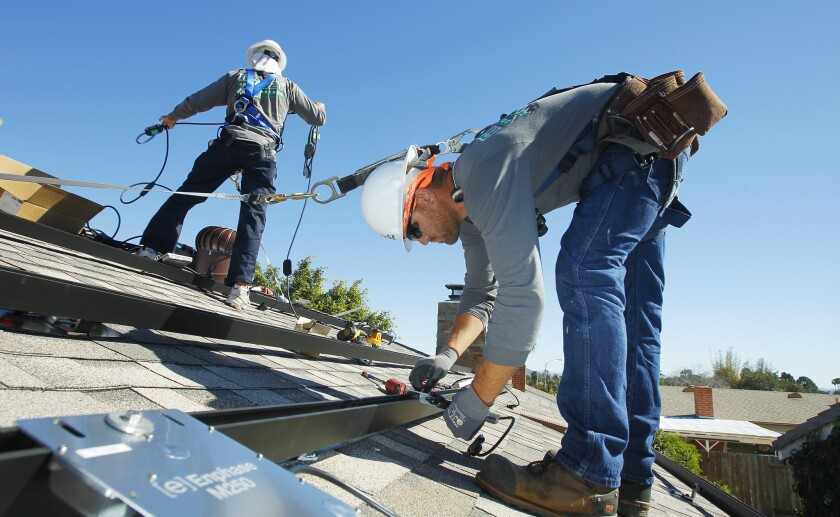 Workers install solar panels on the roof of a home.