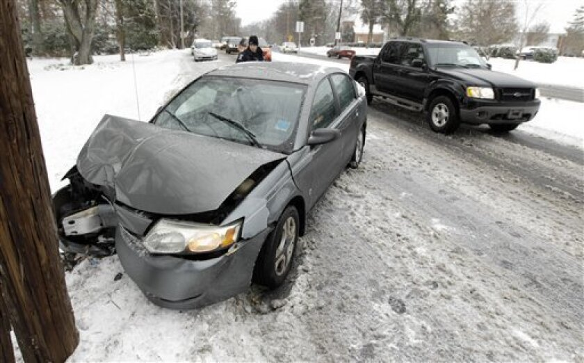 A police officer examines the wreckage of a car after it slid into a power pole during a snowstorm in Charlotte, N.C., Monday, Jan. 10, 2011. Sleet, ice and several inches of snow _ as much as 9 inches in some places _ blanketed states from Louisiana to the Carolinas mostly unaccustomed to arctic weather and caused at least three deaths and left thousands without power. (AP Photo/Chuck Burton)