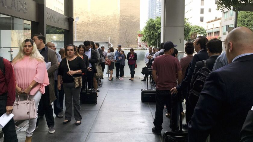 Immigrants awaiting deportation hearings line up last month outside the building that houses the immigration courts in Los Angeles.