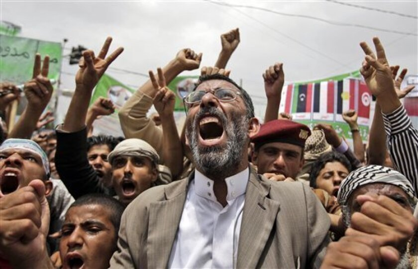 Anti-government protestors, shout slogans during a demonstration demanding the resignation of Yemeni President Ali Abduallah Saleh, in Sanaa, Yemen, Monday, July 4, 2011. (AP Photo/Hani Mohammed)