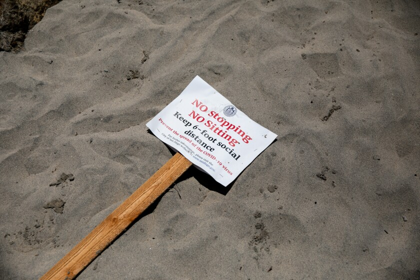 A social distancing advisory lays on the sand at Ocean Beach ahead of Memorial Day Weekend on May 22, 2020 in San Diego, California.