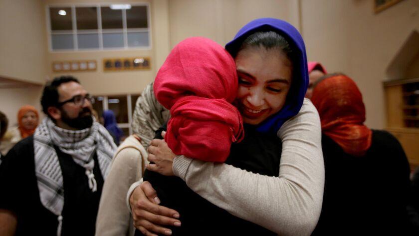 Rida Hamida, left, the main organizer of #IStandWithHijabis, gets a hug from Daisy Campos of Santa Ana at the Islamic Society of Orange County in Garden Grove.