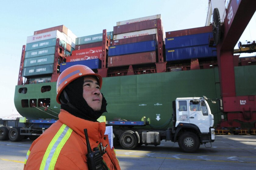 A port worker stands near a container ship at a port in Qingdao in eastern China's Shandong province Monday Feb. 15, 2016. According to customs data released Monday China's trade tumbled in January, in a possible fresh sign of the weakness confronting the world's No. 2 economy. (Chinatopix Via AP)