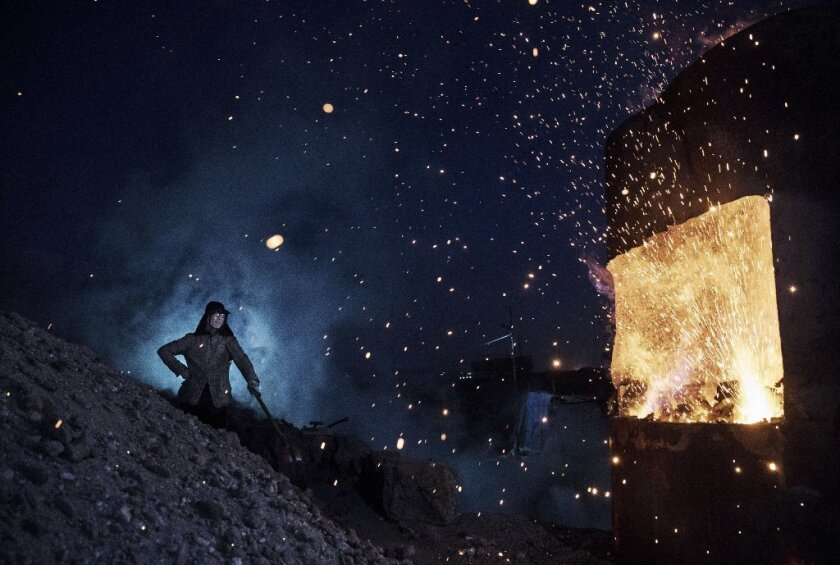 A worker monitors a steel furnace in China's Inner Mongolia. China's excess output is seen as the ch