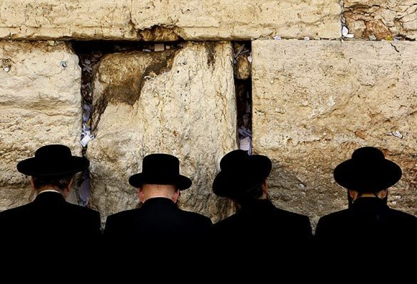 Men pray at Jerusalem's Western Wall before the start of Yom Kippur.