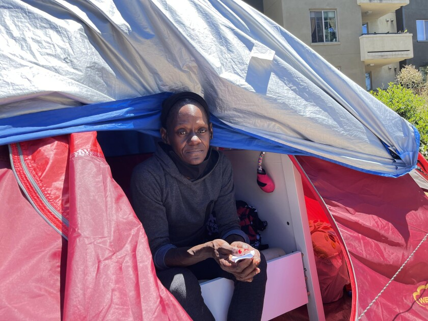 A woman looks out from the opening of a tent.