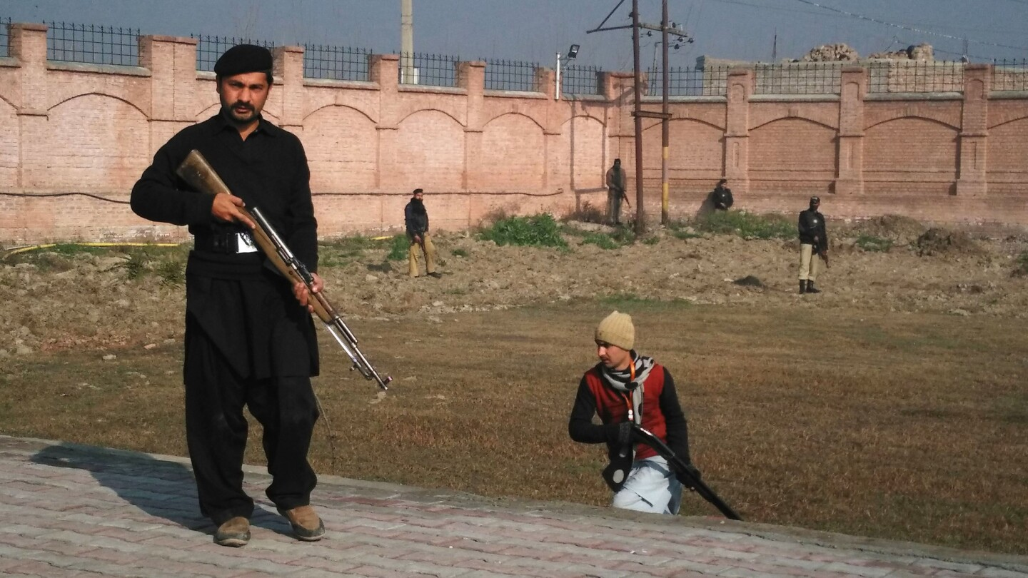 Pakistani security personnel move into position outside Bacha Khan University following an attack by gunmen in Charsadda.