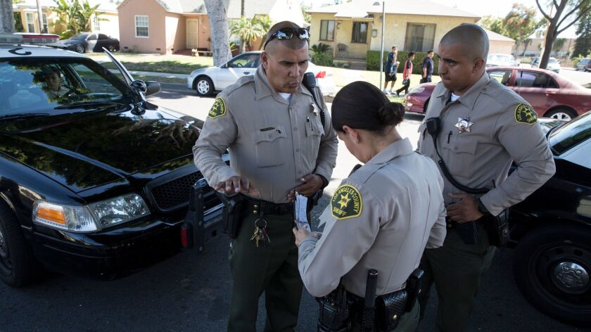 Sheriff's Deputy Marino Gonzalez, left, talks with colleagues while investigating a disturbance in June in Maywood. Senate Bill 54 would establish clear divisions between law enforcement and federal immigration authorities.