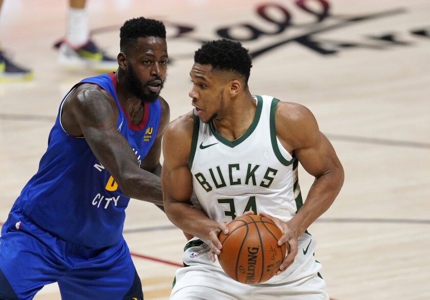 Milwaukee Bucks forward Giannis Antetokounmpo, right, moves to the rim as Denver Nuggets forward JaMychal Green defends in the first half of an NBA basketball game Monday, Feb. 8, 2021, in Denver. (AP Photo/David Zalubowski)