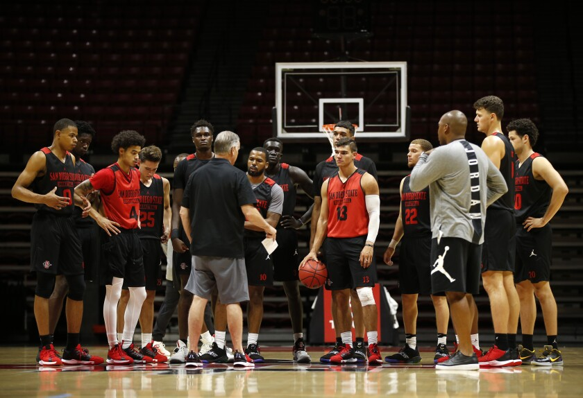 San Diego State University basketball coach Brian Dutcher, center, talks with the Aztecs during a practice on Sept. 26, 2019.