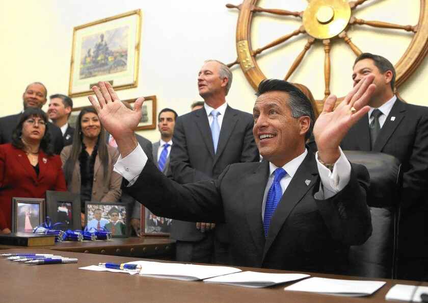 Surrounded by lawmakers and staff members, Nevada Gov. Brian Sandoval signs into law an unprecedented package of incentives to bring Tesla Motors' $5-billion battery factory to the state.