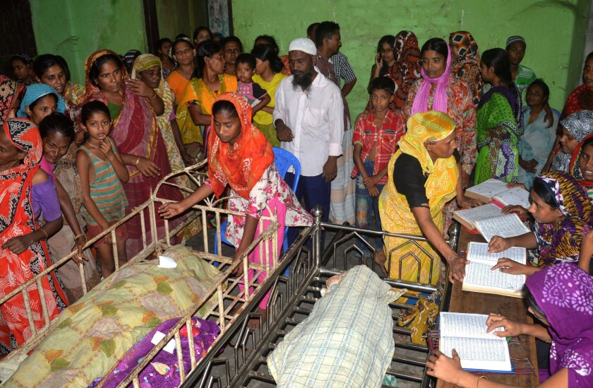 Relatives surround the bodies of some of those killed in a stampede at a charity event in Mymensingh, Bangladesh, on July 10.