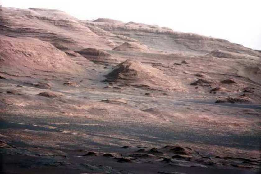 In this image released by NASA on Monday, Aug. 27, 2012, a chapter in the layered geological history of Mars is laid bare. It shows the base of Mount Sharp, the rover's eventual science destination, and is part of a larger image taken by Curiosity's 100-millimeter Mast Camera. Scientists enhanced the color in one version to show the scene under the lighting conditions that exist on Earth, which helps in analyzing the terrain. The pointy mound in the center is about 1,000 feet across and 300 feet high.