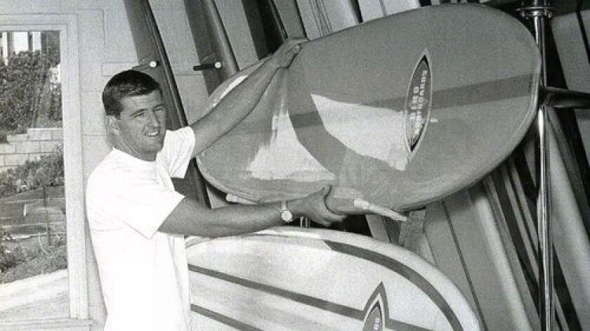 Surfing pioneer Bing Copeland, now 80, shows off some of his handiwork many years ago. Copeland was the longtime owner and boardmaker at Bing Surfboard in Encinitas.