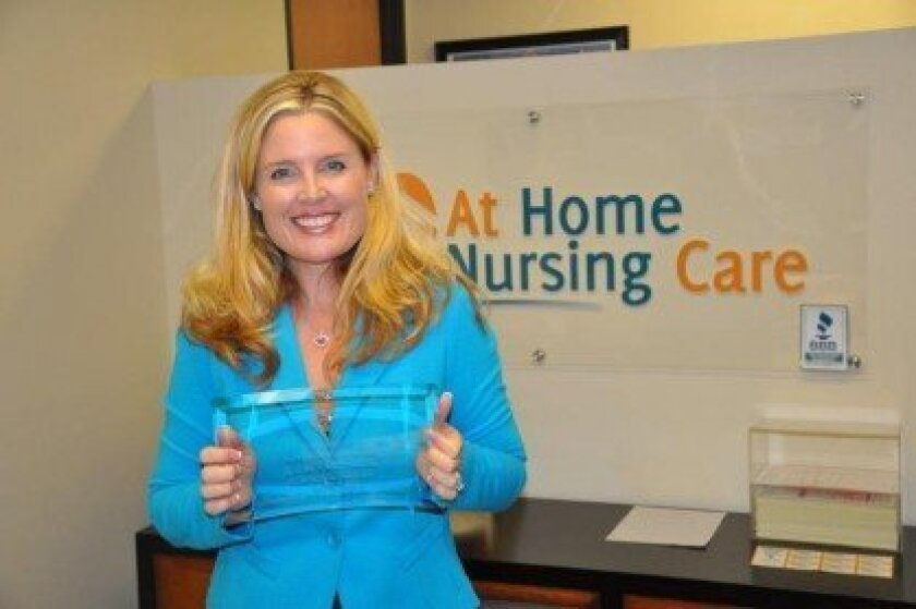 """Lauren Reynolds holds her award for """"Entrepreneur of the Year"""" presented by the San Diego North Chamber of Commerce."""