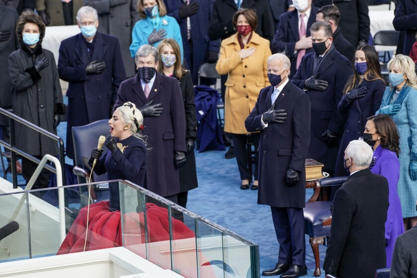 Lady Gaga performs the national anthem while people stand behind her, hand over heart.