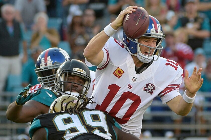 New York Giants quarterback Eli Manning (10) is sacked by Jacksonville Jaguars defensive tackle Sen'Derrick Marks (99) and defensive end Ryan Davis (59) on the Giants' final possession of the second half of an NFL football game in Jacksonville, Fla., Sunday, Nov. 30, 2014. Manning fumbled on the play. The Jaguars won 25-24. (AP Photo/Phelan M. Ebenhack)