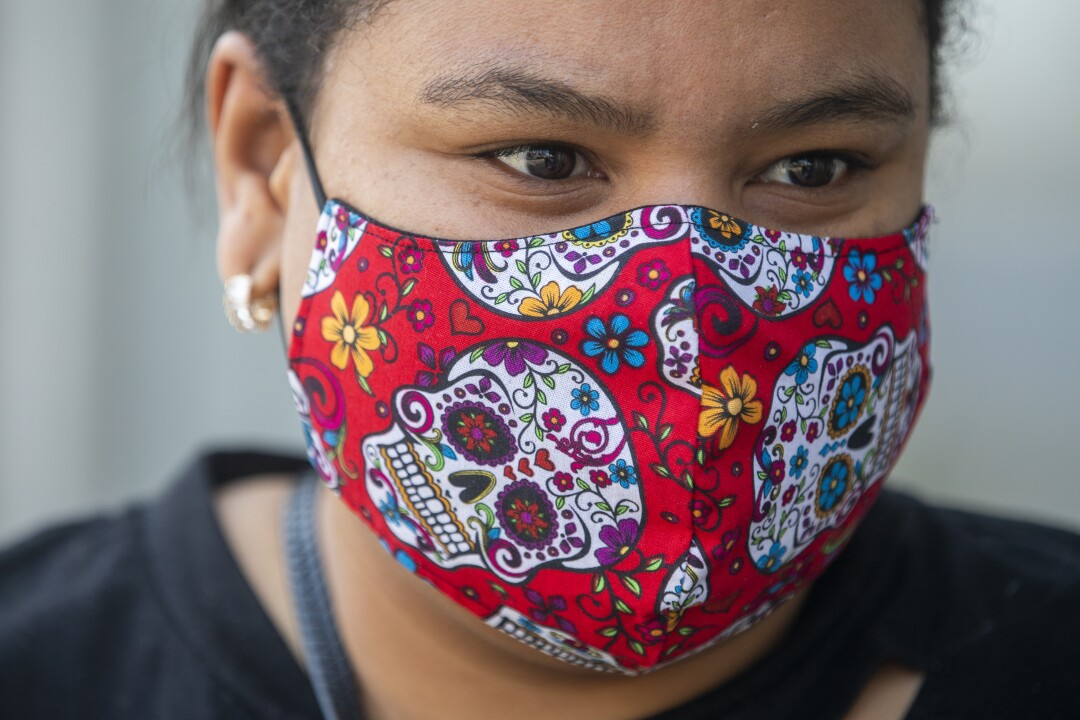 A woman wears a Day of the Dead-style face mask