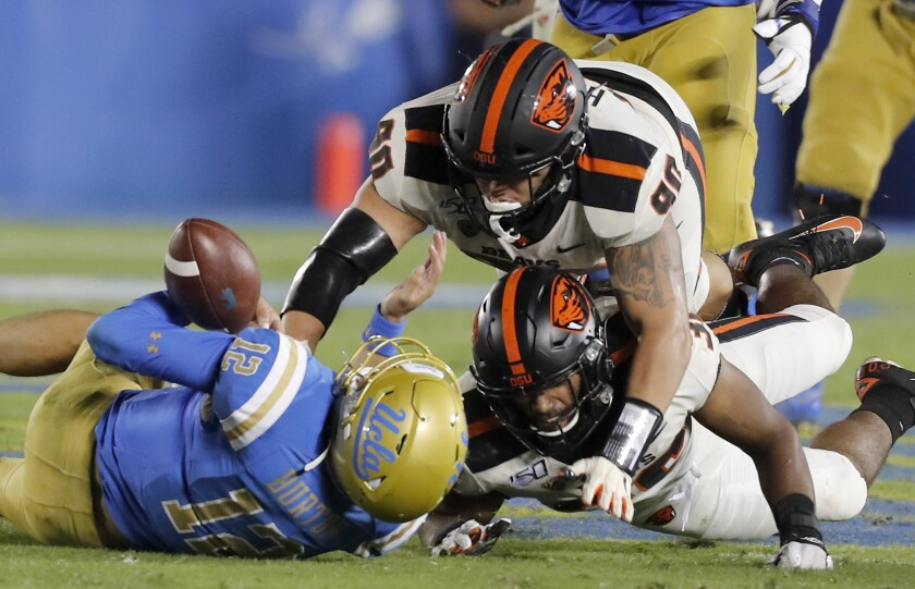 UCLA quarterback Austin Burton is brought down by a pair of Oregon State players in the third quarter Saturday night.
