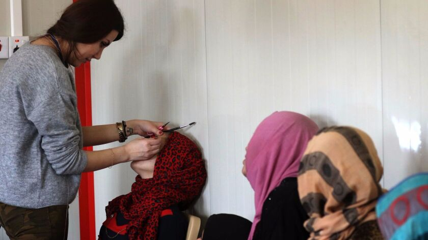 A displaced Iraqi woman, who fled the violence in the northern city of Mosul as a result of a planned operation to retake the city from jihadists, has her eyebrows plucked at a makeshift beauty salon at the Hasan Sham camp on Jan. 18 in the village of Hasan Sham, east of Irbil.