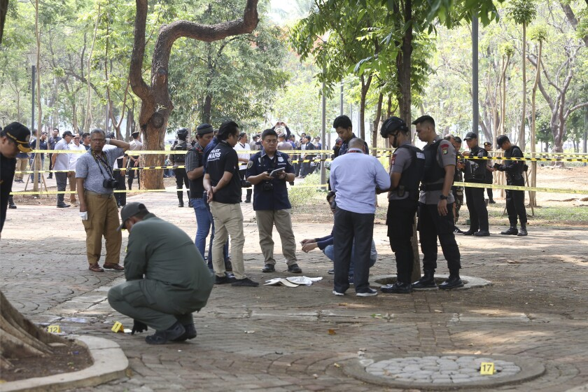 Police investigators inspect the site of an explosion in Jakarta, Indonesia, Tuesday, Dec. 3, 2019. An explosion from a smoke grenade occurred Tuesday near the presidential palace in Indonesia's capital. (AP Photo)