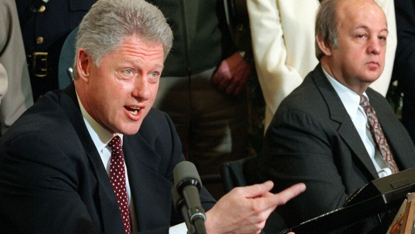 Then-President Clinton holds a news conference on March 5, 1997 to talk about clamping down on gun sales to foreigners. At right is former President Ronald Reagan's press secretary James Brady.