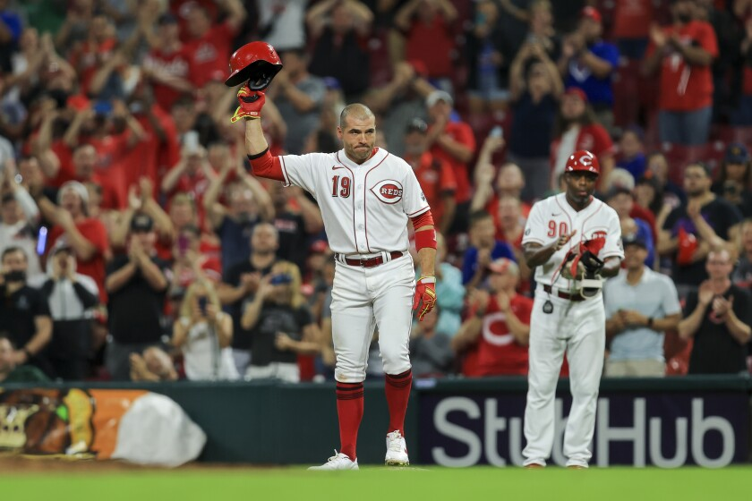 Cincinnati Reds' Joey Votto (19) acknowledges the crowd after hitting a single during the seventh inning of a baseball game against the Chicago Cubs in Cincinnati, Monday, Aug. 16, 2021. The hit was the 2,000th of his career. (AP Photo/Aaron Doster)