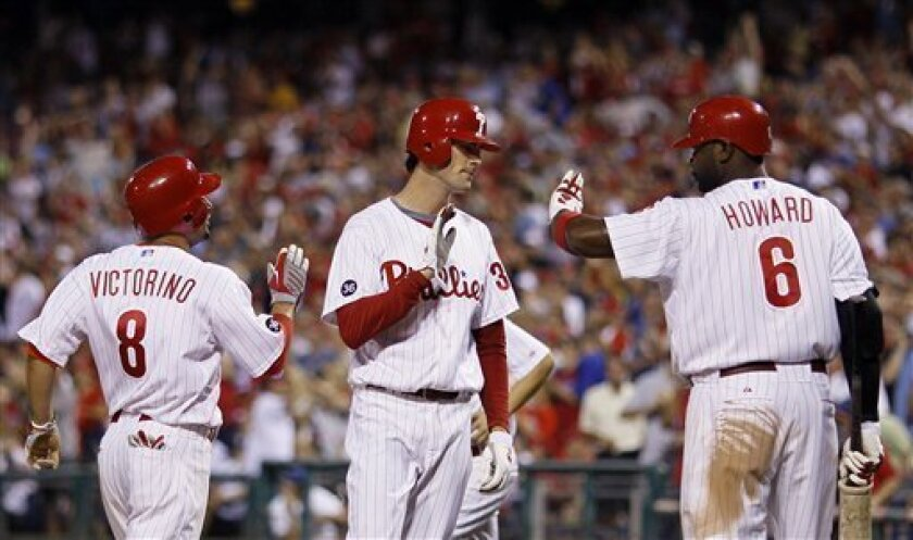 Philadelphia Phillies' Shane Victorino, left, and Cole Hamels, center, celebrate with Ryan Howard after they scored on a two-RBI single by teammate Chase Utley in the fifth inning of a baseball game against the Florida Marlins, Wednesday, Sept. 8, 2010, in Philadelphia. Philadelphia won 10-6. (AP Photo/Matt Slocum)