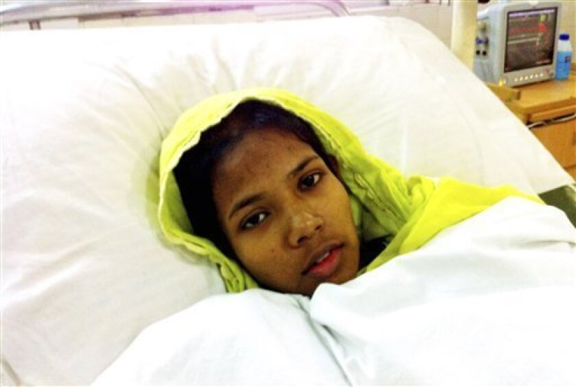 In this photo taken by a mobile phone camera, survivor of a collapsed building Reshma Begum lie down on a bed as she receives treatment at a hospital in Savar, near Dhaka, Bangladesh, Saturday, May 11, 2013. Begum was working in a factory on the second floor of Rana Plaza when the building began collapsing around her April 24. For 17 days, the 19-year-old seamstress lay trapped in a dark basement pocket beneath thousands of tons of wreckage as temperatures outside climbed into the mid-30s Celsiu