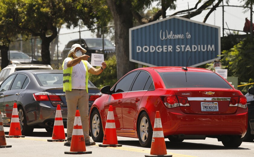 Workers confirm that drivers have an appointment for coronavirus testing that resumed at Dodger Stadium this week.