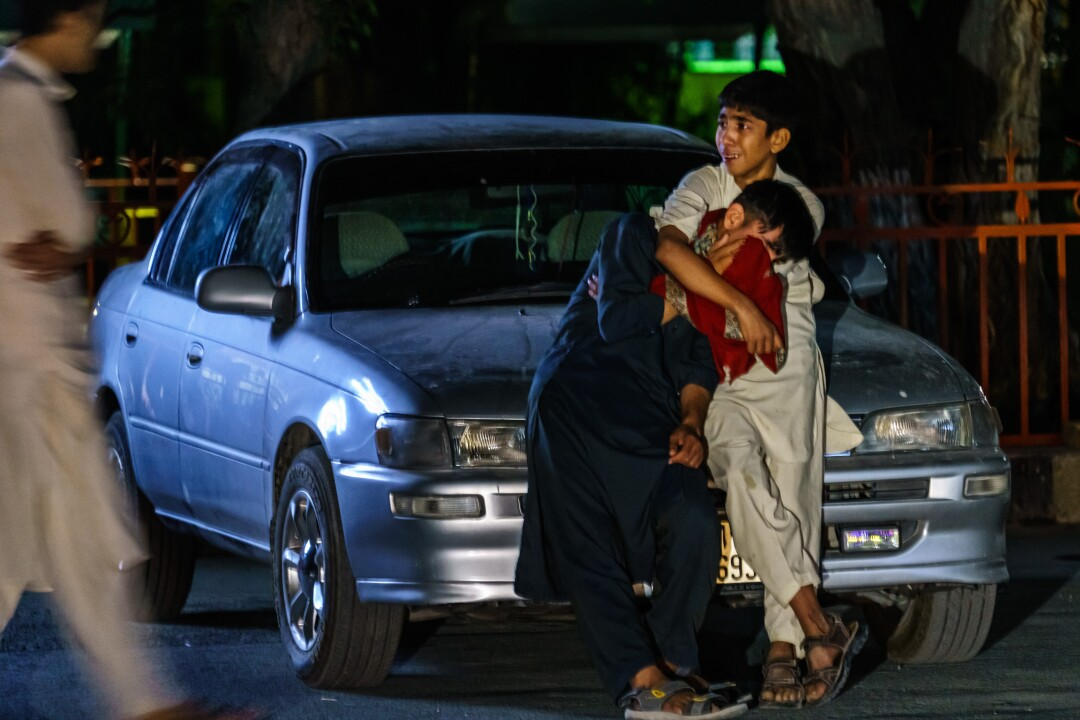 Two boys embrace each other as they weep in the parking lot at Wazir Akbar Khan hospital in Kabul