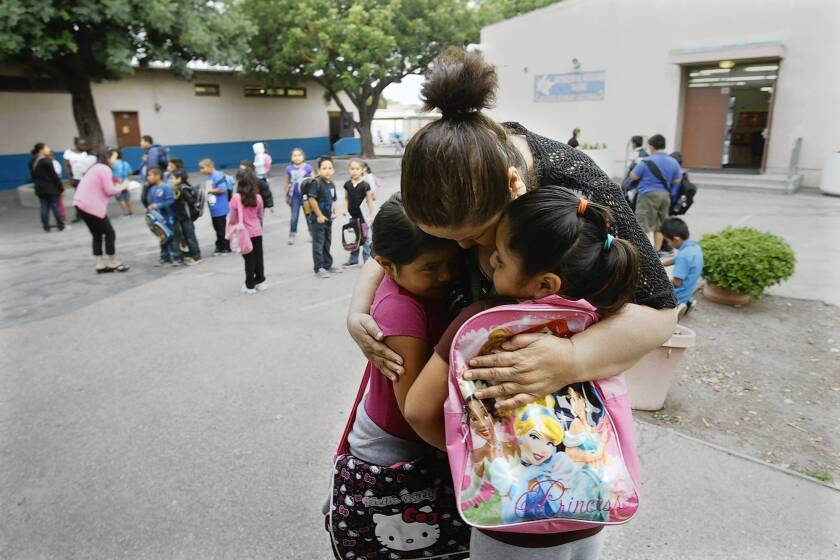 Irma Cobian, principal at Weigand Avenue Elementary in Watts, hugs first-graders Amy Mukul, left, and Shelly Canul. The school board voted last week to accept a parent petition to remove the popular Cobian from the low-performing school. In a show of loyalty to Cobian, 21 of 22 teachers have requested transfers, causing more turmoil for the campus.