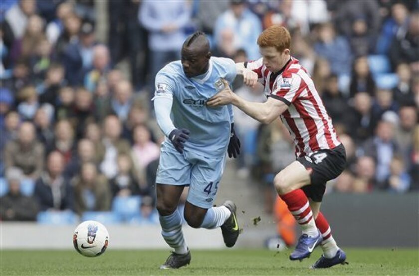 Manchester City's Mario Balotelli, center, fights for the ball against Sunderland's Jack Colback during their English Premier League soccer match at The Etihad Stadium, Manchester, England, Saturday, March 31, 2012. (AP Photo/Jon Super)