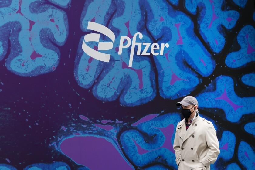 Un hombre camina junto al edificio del gigante farmacéutico Pfizer