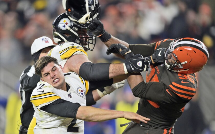 Browns' Myles Garrett swings his helmet at Steelers quarterback Mason Rudolph.