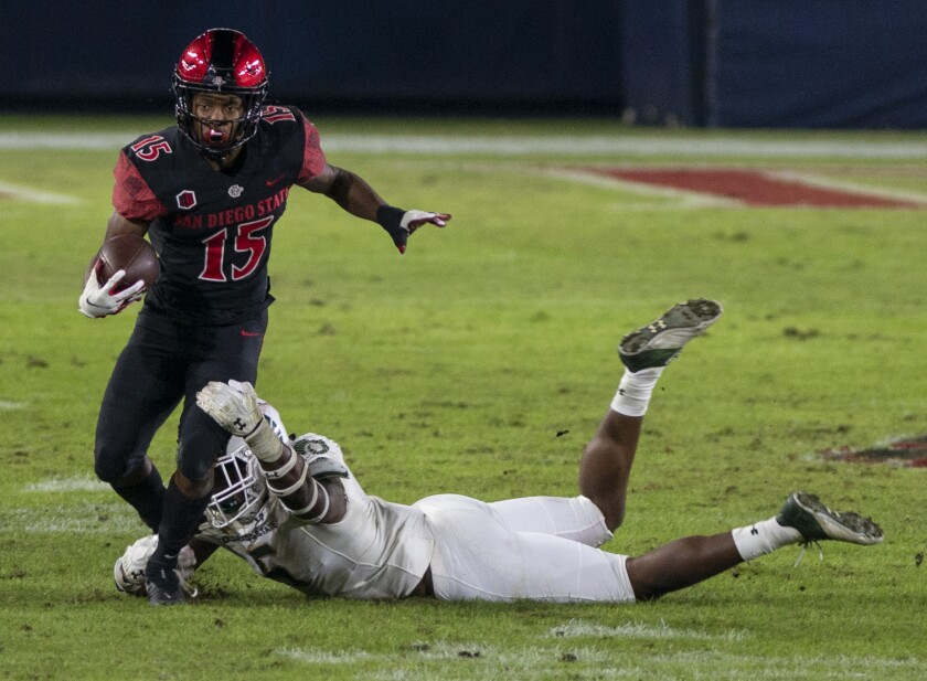 San Diego State's Jordan Byrd tries to break the tackle by Colorado State's Dequan Jackson.