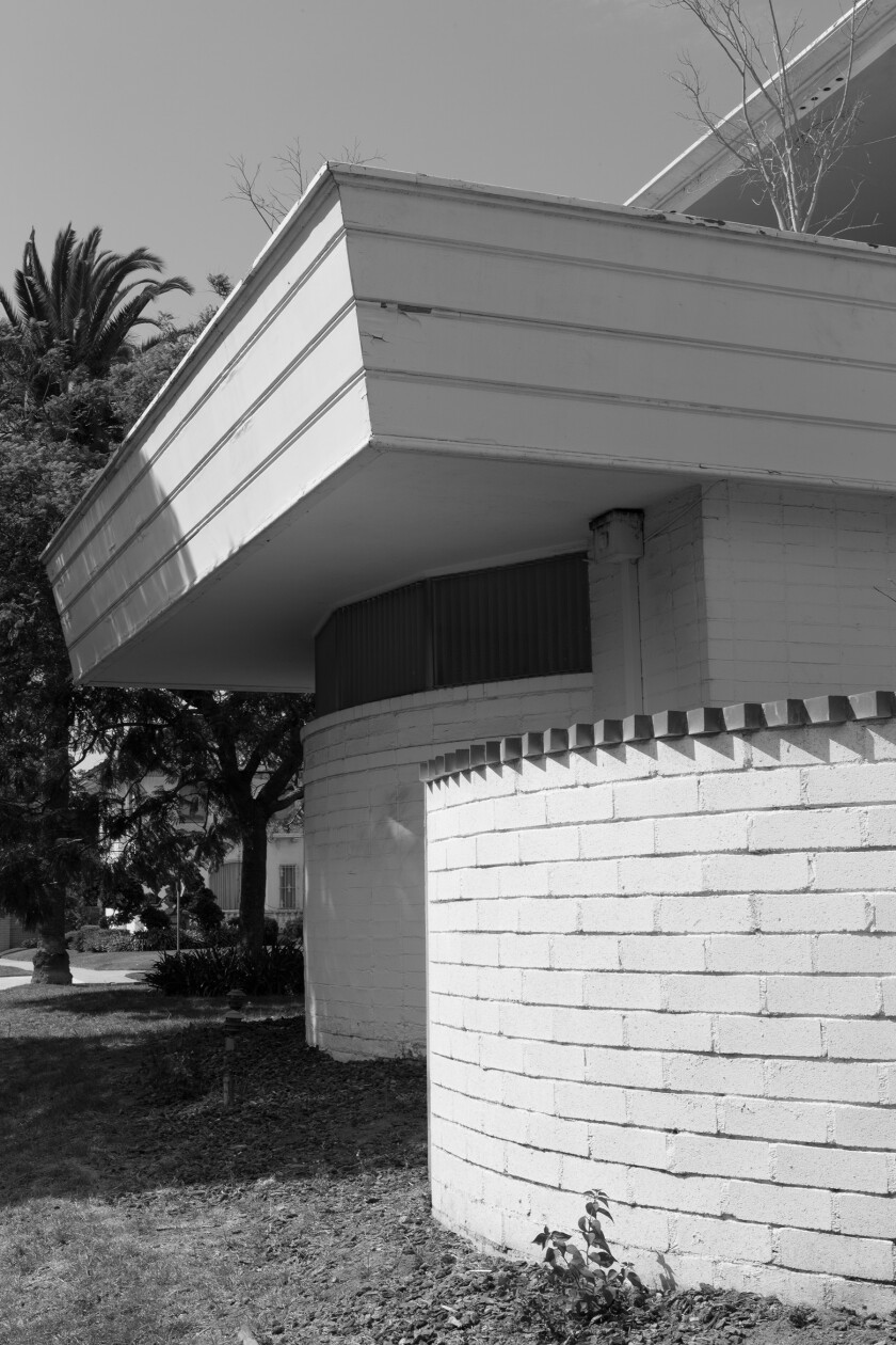 A black-and-white image of the Paul Williams Residence shows a curving wall with a serrated edge.
