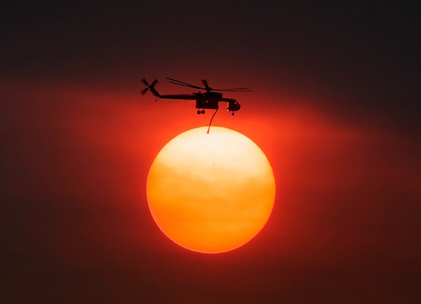 Smoke from the Mountain fire obscures the sun Thursday as a helicopter heads to battle the blaze.